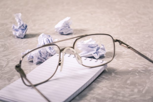 close-up-photography-of-eyeglasses-near-crumpled-papers-963056